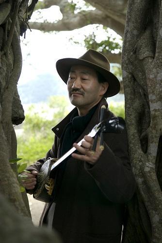 奄美のガジュマル樹の胎内で三線を弾き歌う今福龍太