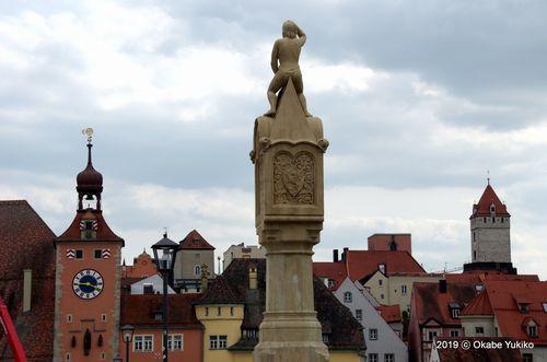 塔が林立する町を眺める石橋の石像